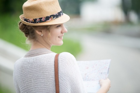 Young traveler woman in straw hat holding map. Back side view